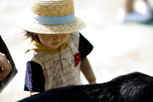 日差しの中で麦わら帽子をかぶった子供