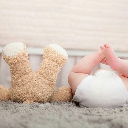 おむつをはいた赤ちゃんとぬいぐるみ