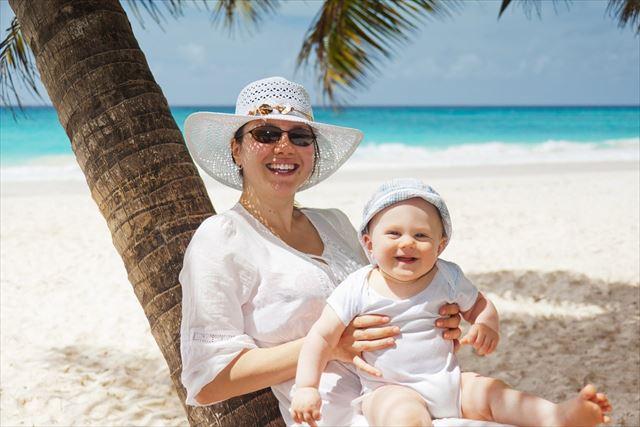 おすわりする生後6ヶ月の赤ちゃんと母親の画像